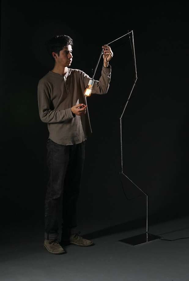 Steve Sanchez with the stainless steel Up Lamp by fellow CCA student Jessie Fritts (furniture, 2014).