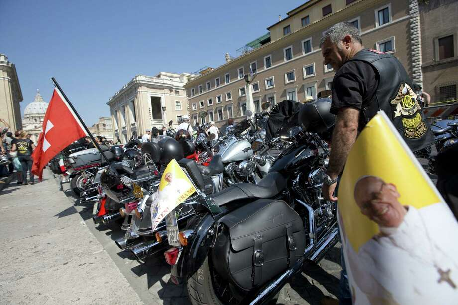 Harley-Davidson riders park their bikes on Via della Conciliazione, the main street leading to the Vatican, as they wait for Pope Francis to bless them ahead of Mass in St. Peter's Square. Photo: Andrew Medichini / Associated Press