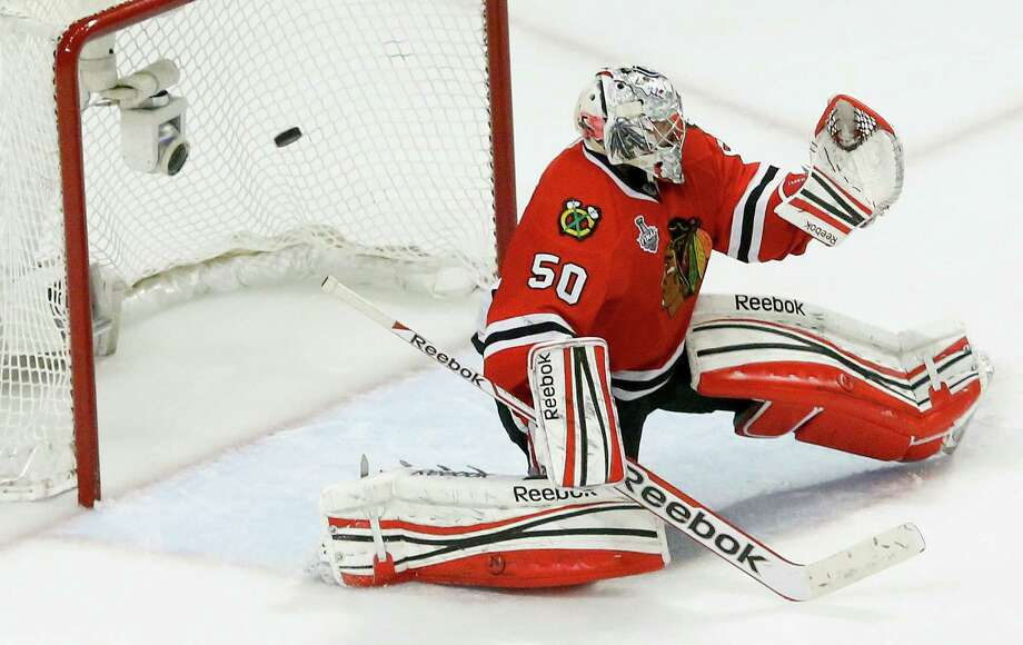 Blackhawks goalie Corey Crawford couldn't catch up with a shot by the Bruins' Daniel Paille that ended Game 2 of the Stanley Cup finals in the first overtime period Saturday night at Chicago. Photo: Charles Rex Arbogast, STF / AP