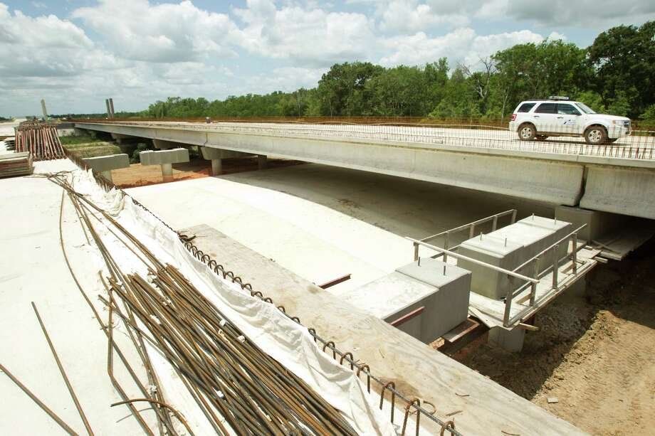 A TxDot vehicle travels over a bridge that spans a Native American burial ground, that was sealed with a slab of cement along the route of the Grand Parkway Friday, May 31, 2013, northwest of Houston. Photo: Brett Coomer, Houston Chronicle / © 2013 Houston Chronicle