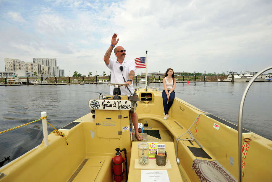 Captain Frank Fumega pilots the Harbor Point Water Taxi accross the West Branch of Stamford Harbor with his first mate Kayla McCabe on Sunday, June 16, 2013. Photo: Jason Rearick / Stamford Advocate