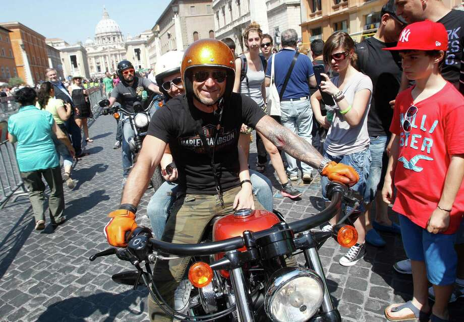 Harley-Davidson riders parade in Via della Conciliazione leading to St. Peter's Square during a Mass celebrated by Pope Francis, at the Vatican, Sunday, June 16, 2013. Pope Francis on Sunday blessed thousands of Harley Davidsons and their riders as the American motorcycle manufacturer celebrated its 110th anniversary with a loud parade and plenty of leather. (AP Photo/Riccardo De Luca) Photo: Riccardo De Luca, Associated Press / AP