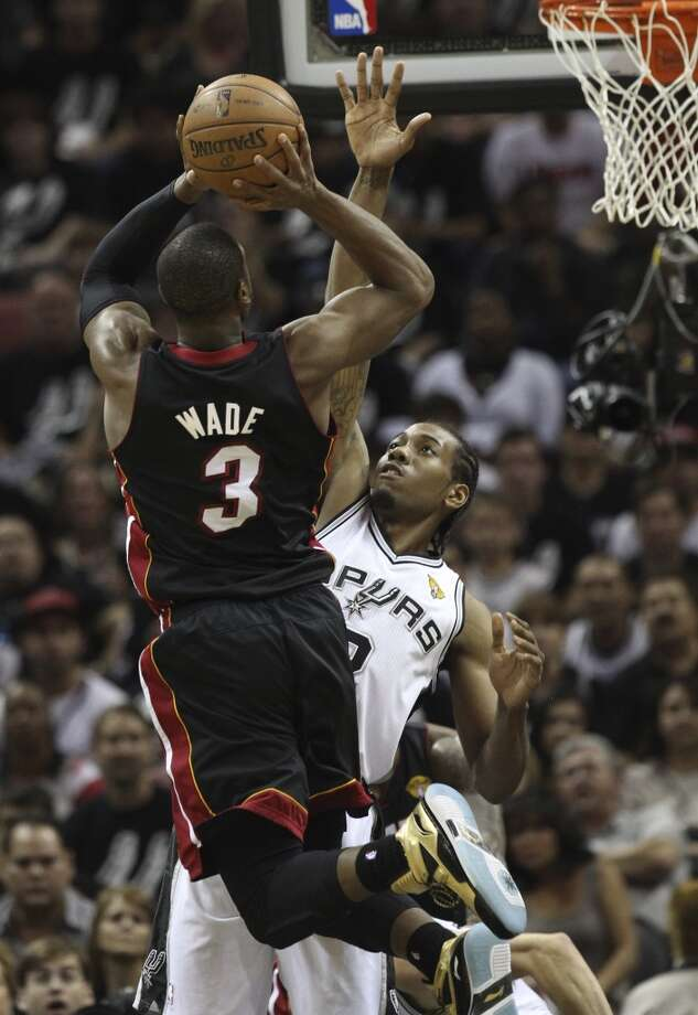 Miami Heat's Dwyane Wade shoots over the defense of San Antonio Spurs' Kawhi Leonard during the first half of Game 5 of the NBA Finals at the AT&T Center on Sunday, June 16, 2013. (Kin Man Hui/San Antonio Express-News)