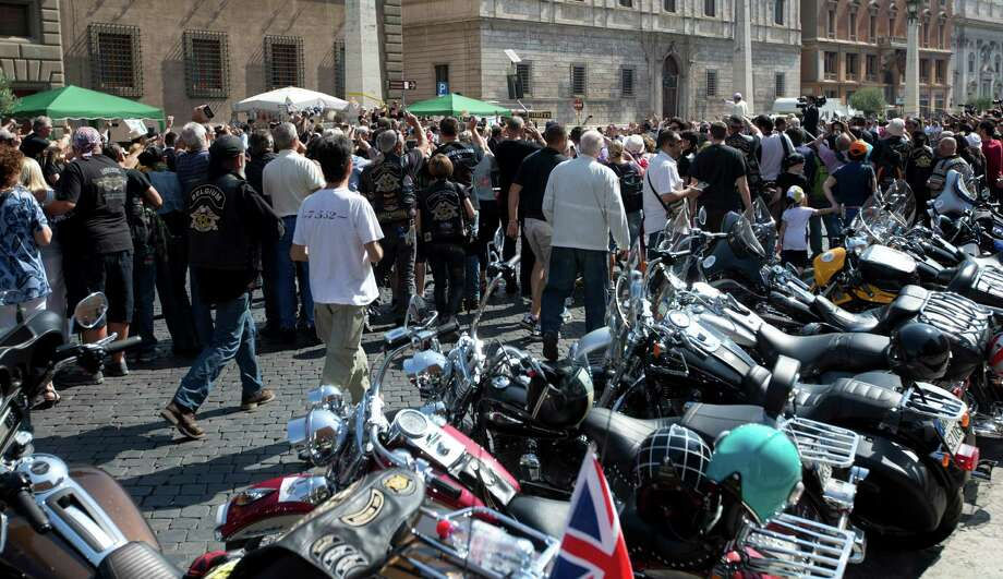 Harley Davidson motorcycles are parked as Pope Francis, white figure seen above the crowd at top right, arrives to celebrate mass in St. Peter's Square, at the Vatican, Sunday, June 16, 2013. Thousands of Harley-Davidson lovers have met in Rome to celebrate the motorcycle company's 110th anniversary. The four-day event includes a major parade through the heart of the city and a blessing by Pope Francis during his Angelus noon prayer at the Vatican on Sunday.  (AP Photo/Andrew Medichini) Photo: Andrew Medichini, Associated Press / AP