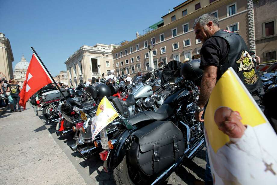 Harley Davidson motorcycles riders park their motorcycles in Via della Conciliazione leading to the Vatican, seen at left, as they wait for Pope Francis to drive by to bless them ahead of mass in St. Peter's Square, at the Vatican, Sunday, June 16, 2013. The riders are gathered in Rome for a four-day event to celebrate the motorcycle company's 110th anniversary.  (AP Photo/Andrew Medichini) Photo: Andrew Medichini, Associated Press / AP