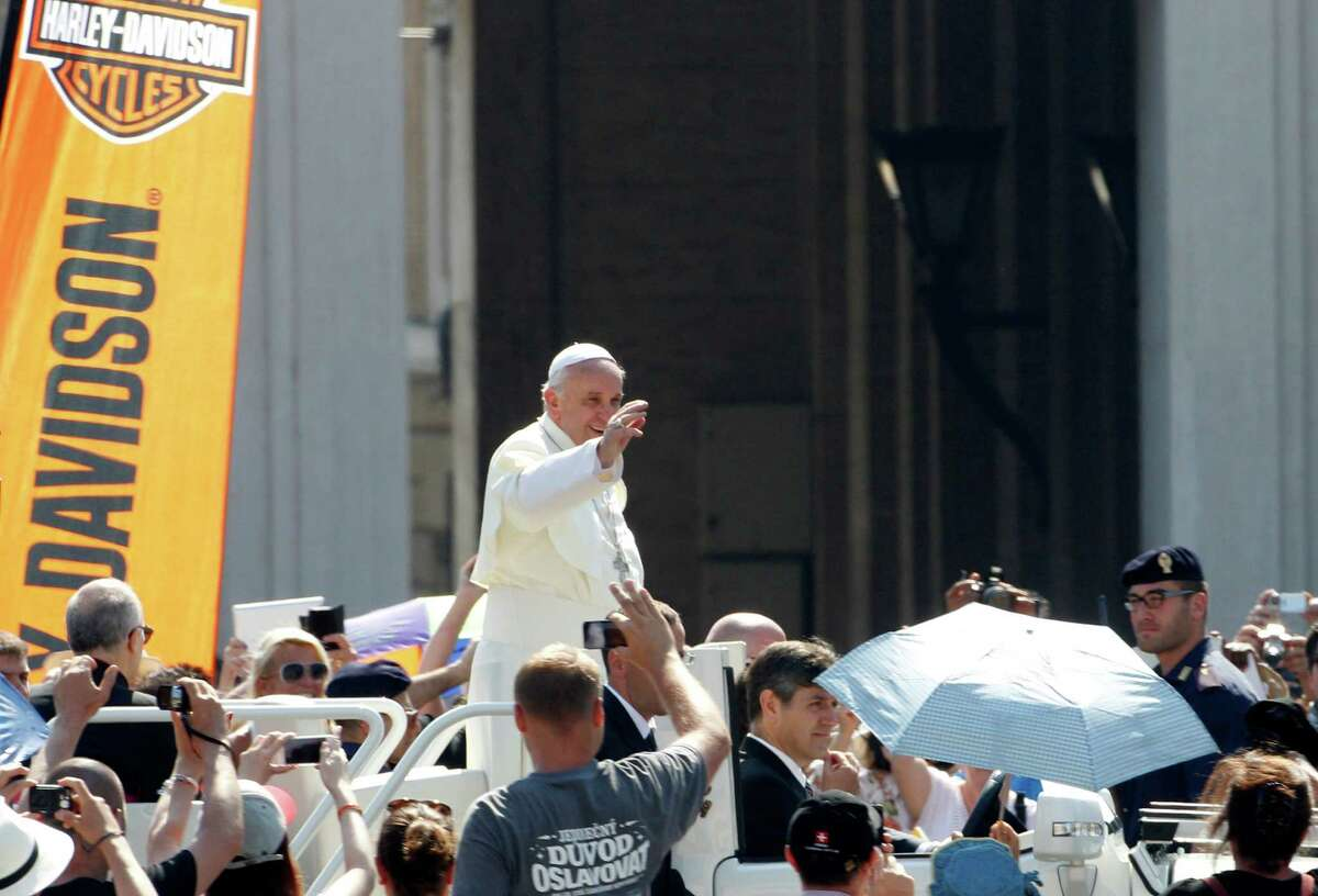Pope Francis waves to faithful as he arrives for a Mass in St. Peter's Square at the Vatican, Sunday, June 16, 2013. The pontiff greeted hundreds of Harley Davidson riders and blessed their motorcycles prior to the start of the mass. The riders are gathered in Rome for a four-day event to celebrate the motorcycle company's 110th anniversary. (AP Photo/Riccardo De Luca)