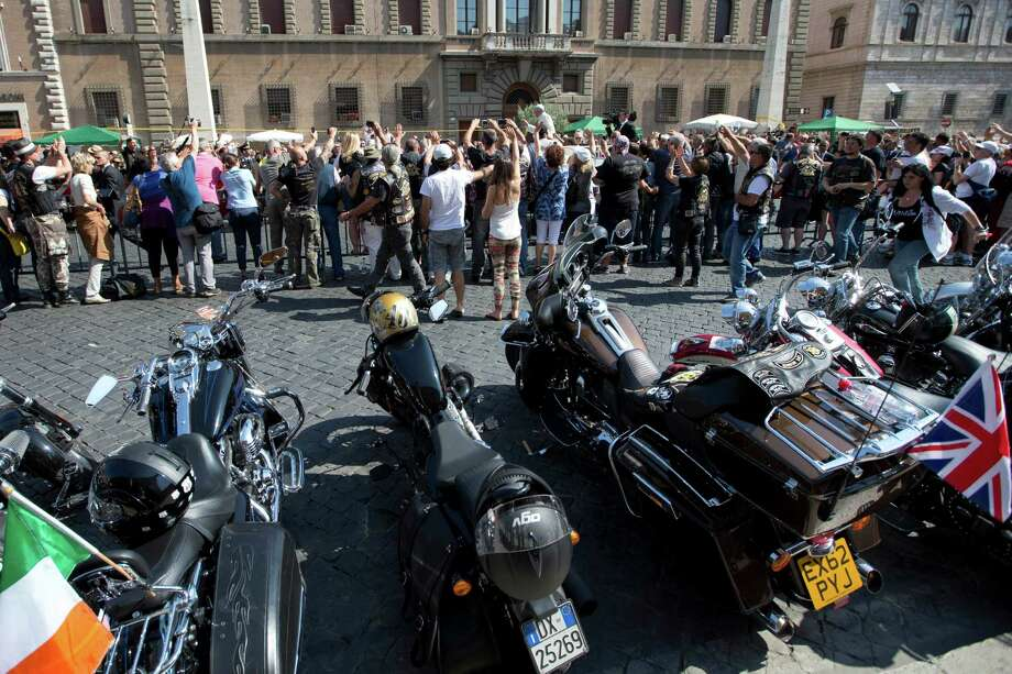 Harley Davidson motorcycles are parked as Pope Francis, top, arrives to celebrate mass in St. Peter's Square, at the Vatican, Sunday, June 16, 2013. Thousands of Harley-Davidson lovers have met in Rome to celebrate the motorcycle company's 110th anniversary. The four-day event includes a major parade through the heart of the city and a blessing by Pope Francis during his Angelus noon prayer at the Vatican on Sunday.  (AP Photo/Andrew Medichini) Photo: Andrew Medichini, Associated Press / AP