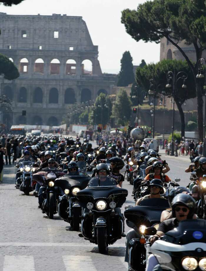 Harley Davidson motorcycles parade through the center of Rome, Saturday, June 15, 2013. Thousands of of Harley-Davidson lovers are meeting in Rome to celebrate the motorcycle company's 110th anniversary. The four-day event includes a major parade through the heart of the city and a blessing by Pope Francis during his Angelus noon prayer at the Vatican on Sunday.  In background is Rome's Colosseum. (AP Photo/Andrew Medichini) Photo: Andrew Medichini, Associated Press / AP