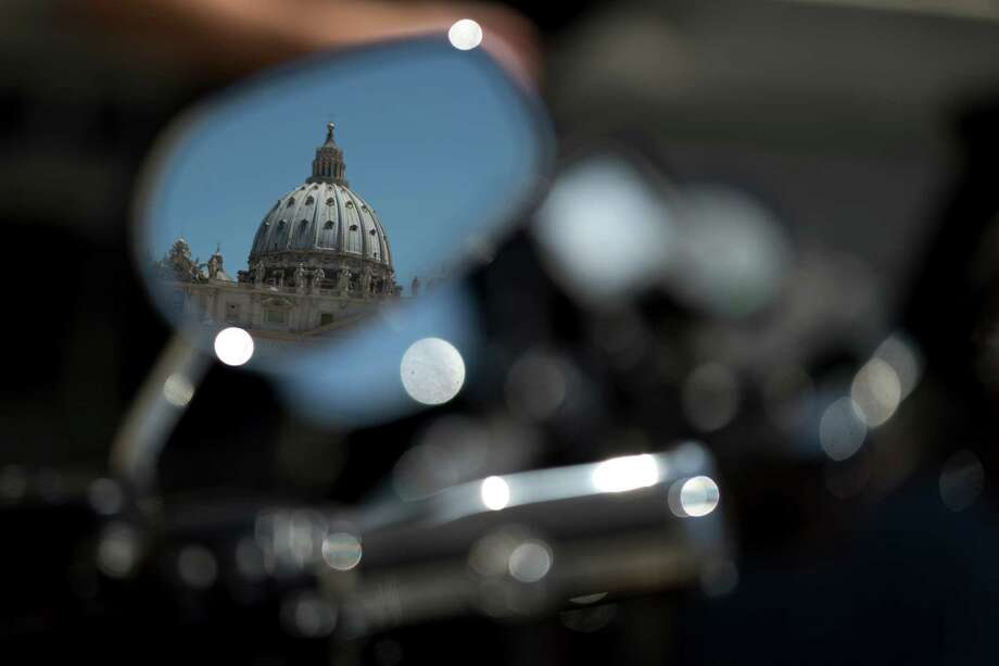 St. Peter's Basilica is reflected in the rear mirror of a Harley-Davidson motorcycle, in Rome, Thursday, June 13, 2013. Thousands of of Harley-Davidson lovers are expected to meet in Rome to celebrate the motorcycle company's 110th anniversary. The four-day event includes a major parade through the heart of the city and a blessing by Pope Francis during his Angelus noon prayer at the Vatican on Sunday. (AP Photo/Andrew Medichini) Photo: Andrew Medichini, Associated Press / AP