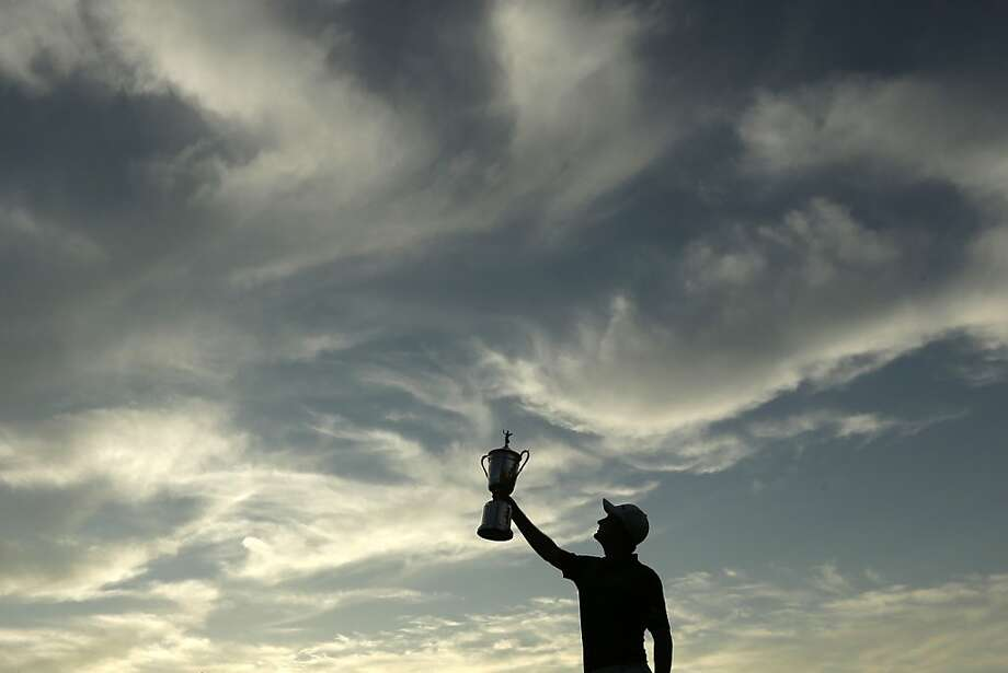 England's Justin Rose cuts a championship silhouette as he holds the trophy aloft after winning the U.S. Open by two strokes. Photo: Charlie Riedel, Associated Press