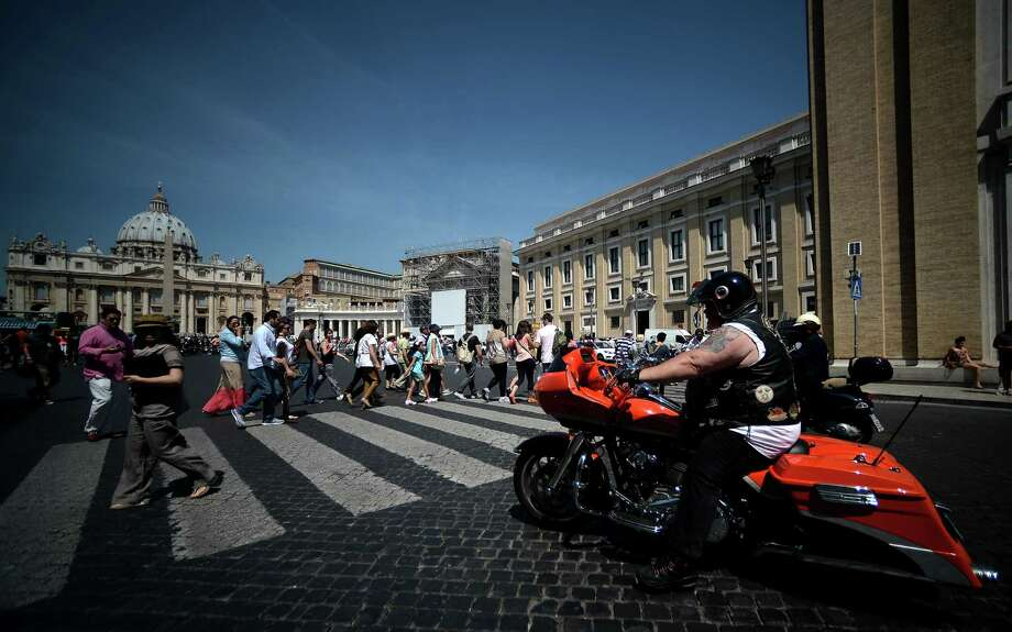 A Harley-Davidson motorbiker rides by the Vatican during 110th Anniversary event in Rome on June 14, 2013. Around 100,000 Harley-Davidson owners arrived on Rome to celebrate the motorcycle's 110th anniversary. The highlight of the four-day meeting will be the blessing by Pope Francis in St Peter's Square on 16 June. Photo: FILIPPO MONTEFORTE, AFP/Getty Images / AFP