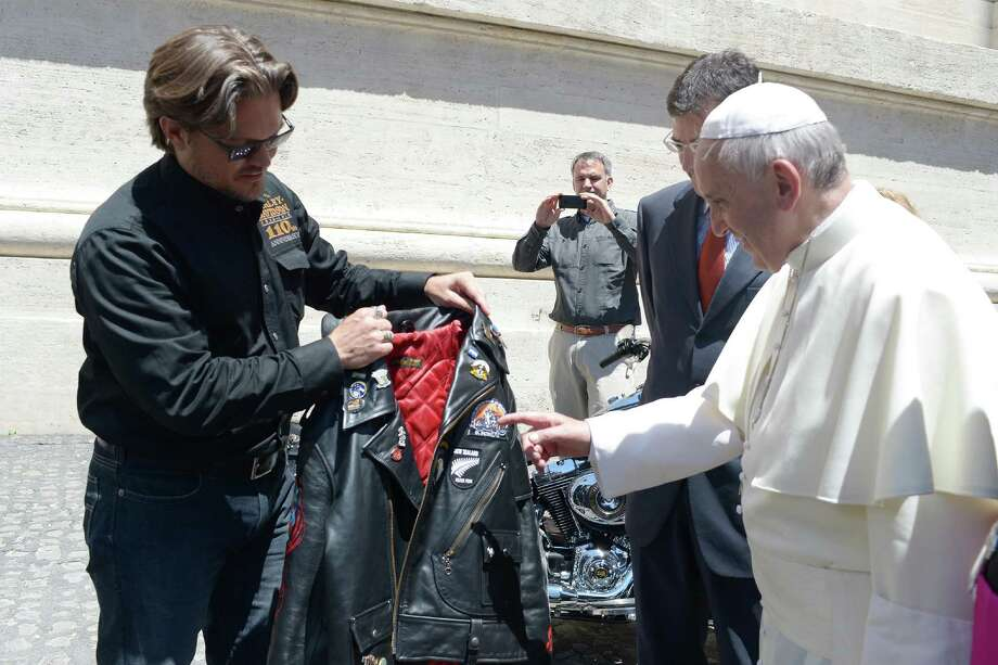 Pope Francis is shown a leather jacket from Harley Davidson Motor Company senior vice-president Mark Hans-Richer, at the Vatican, Wednesday, June 12, 2013. Photo: L'Osservatore Romano, Associated Press / L'Osservatore Romano
