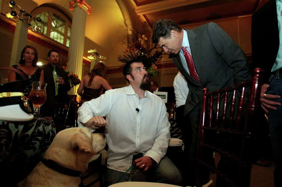 Gov. Rick Perry talks with retired U.S. Navy SEAL Marcus Luttrell next to Luttrell's dog Rigby before Perry spoke to an audience of more than 200 during the Lone Survivor Foundation's 2011 Second Annual Gala titled Mission: Never Quit at Minute Maid Park Saturday, Sept. 17, 2011, in Houston.  Featured speakers included Perry, Luttrell and retired U.S. Army Ranger Capt. Chad Fleming. The Lone Survivor Foundation was established in 2010 by Luttrell in an effort to give back to those that have served in the U.S. military. Photo: Johnny Hanson, Houston Chronicle / © 2011 Houston Chronicle