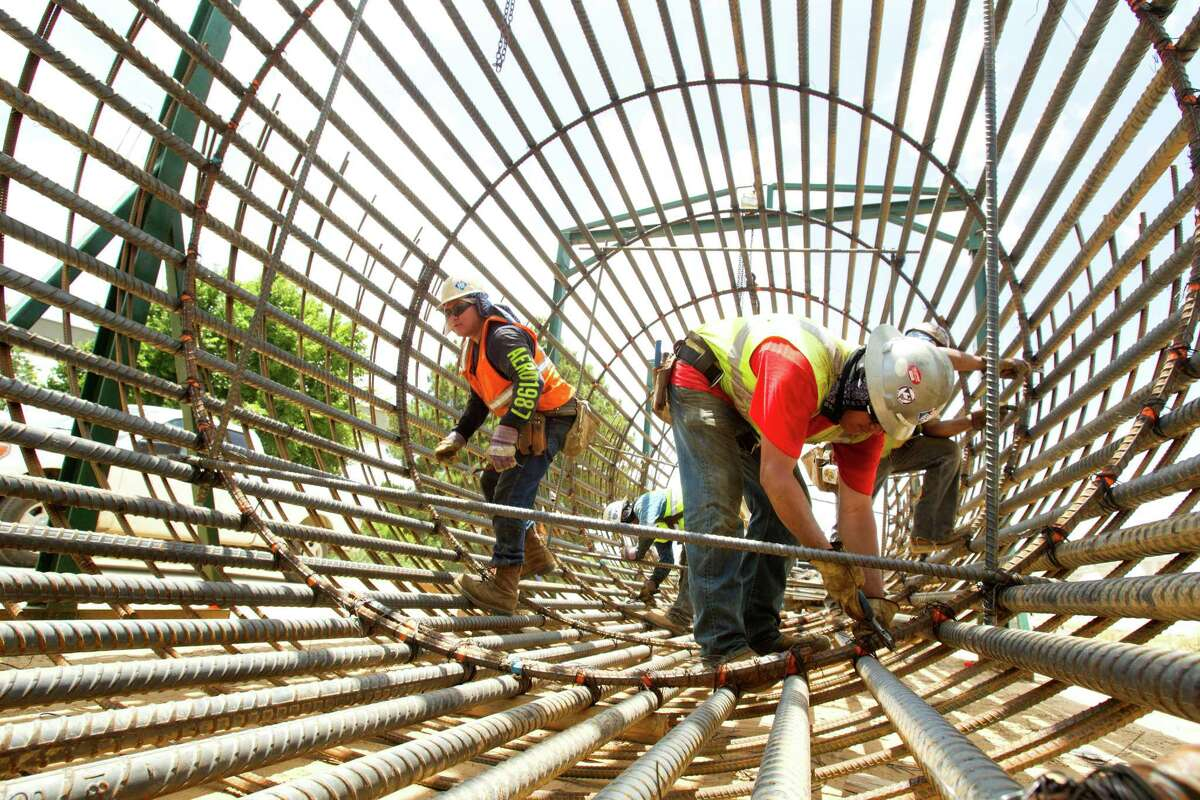 Construction crews build a form for a drill shaft that will be buried 95 feet into the ground to support a connector bridge.