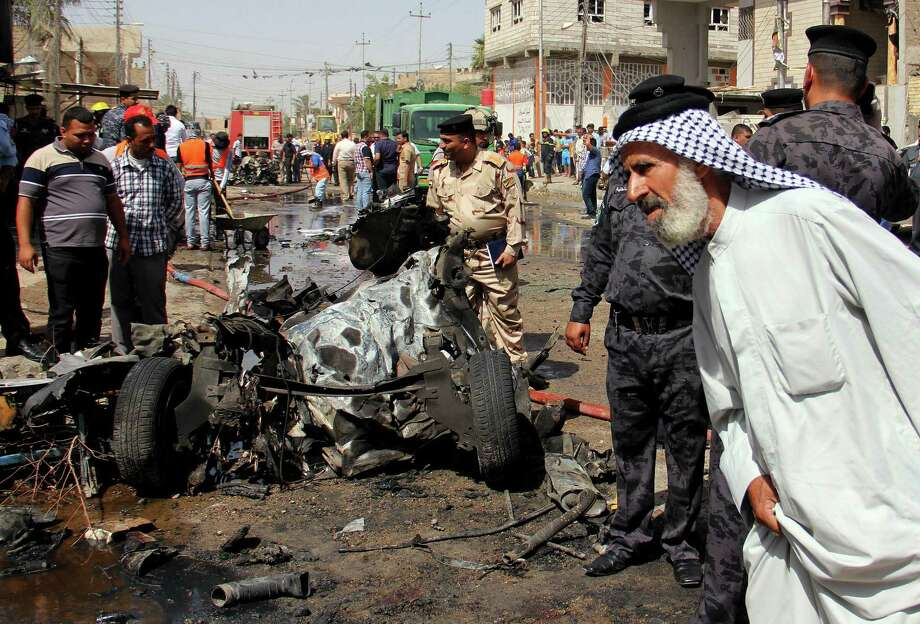 Iraqis inspect mangled wreckage after car bombs struck the oil-rich city of Basra. Coordinated bombings across the nation might have been the work of al-Qaida in Iraq. Photo: Nabil Al-Jurani / Associated Press