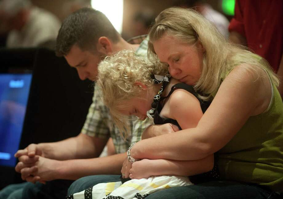 Lara Stern, right, prays with her daughter, Alana, 8, and husband Samuel Stern Sunday, June 16, 2013 during a community prayer and praise worship service at First Baptist Church on Black Forest Road northeast of Colorado Springs, Colo. The Stern family and at least ten other families at the church lost their homes to the Black Forest fire. (AP PHOTO/THE GAZETTE,MARK REIS) Photo: MARK REIS,