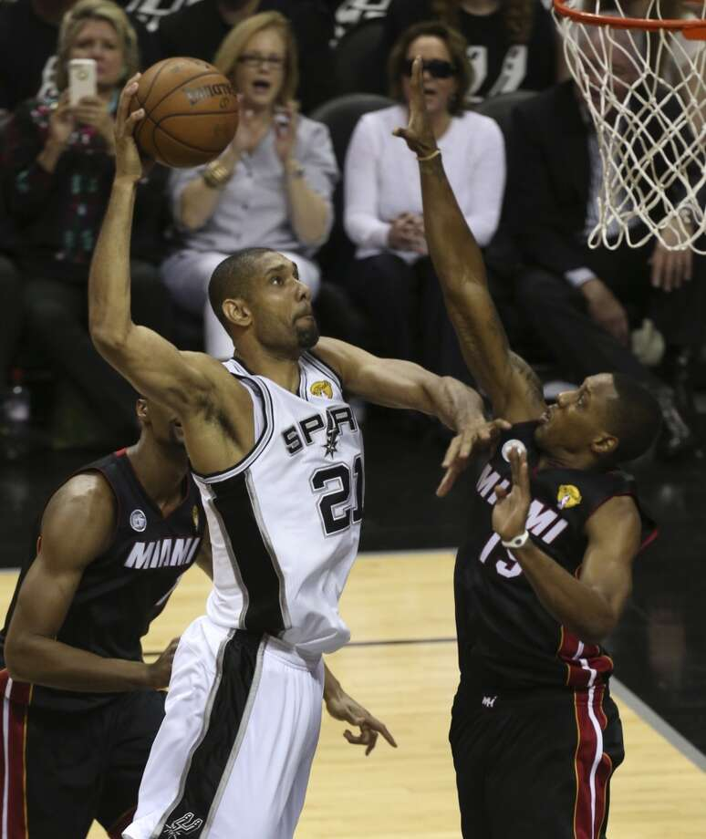 San Antonio Spurs' Tim Duncan flies for a dunk over Miami Heat's Mario Chalmers during the fist half of Game 5 of the NBA Finals at the AT&T Center on Sunday, June 16, 2013. (Jerry Lara/San Antonio Express-News)