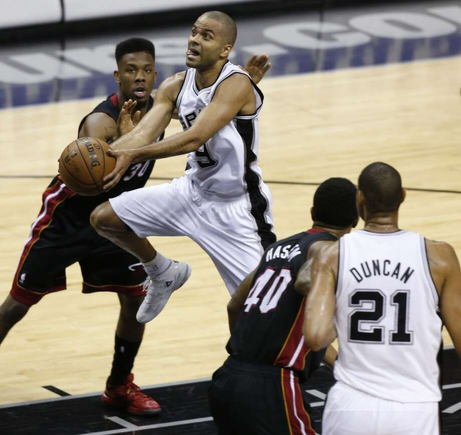 San Antonio Spurs' Tony Parker drives past Miami Heat's Norris Cole on his way to the hoop during first half action in Game 5 of the 2013 NBA Finals Sunday June 16, 2013 at the AT&T Center. Also seen are San Antonio Spurs' Tim Duncan and Miami Heat's Udonis Haslem. (Edward A. Ornelas/San Antonio Express-News)