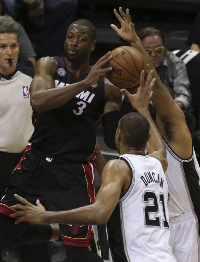 Miami Heat's Dwyane Wade looks to dish out from under the goal while under pressure from San Antonio Spurs' Tim Duncan during the fist half of Game 5 of the NBA Finals at the AT&T Center on Sunday, June 16, 2013. (Jerry Lara/San Antonio Express-News)