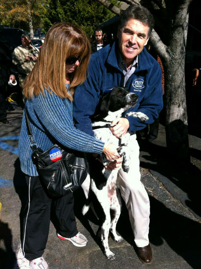 "Perry poses with Beauregard the rescue dog in January while campaigning in South Carolina. A report from ABC News on Jan. 14 said Perry had been courting the approval of the dogs as much as the human's - when someone said their dog supported Perry he responded with, ""They all are. Dogs have the best instincts."""