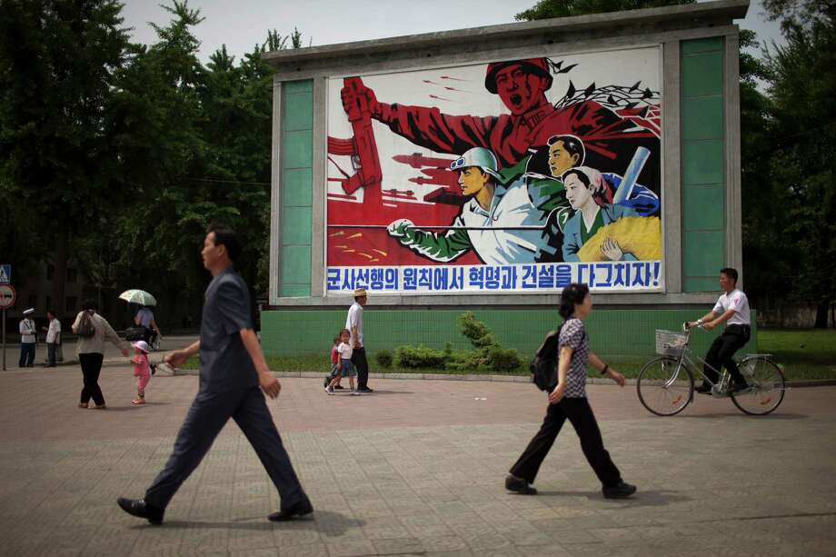 "People walk past a roadside propaganda billboard promoting the ""military first"" policy and a boost to build the country's economy in Pyongyang, North Korea, Sunday, June 16, 2013. North Korea's top governing body on Sunday proposed high-level nuclear and security talks with the United States in an appeal sent just days after calling off talks with rival South Korea. (AP Photo/Alexander Yuan) Photo: Alexander Yuan"