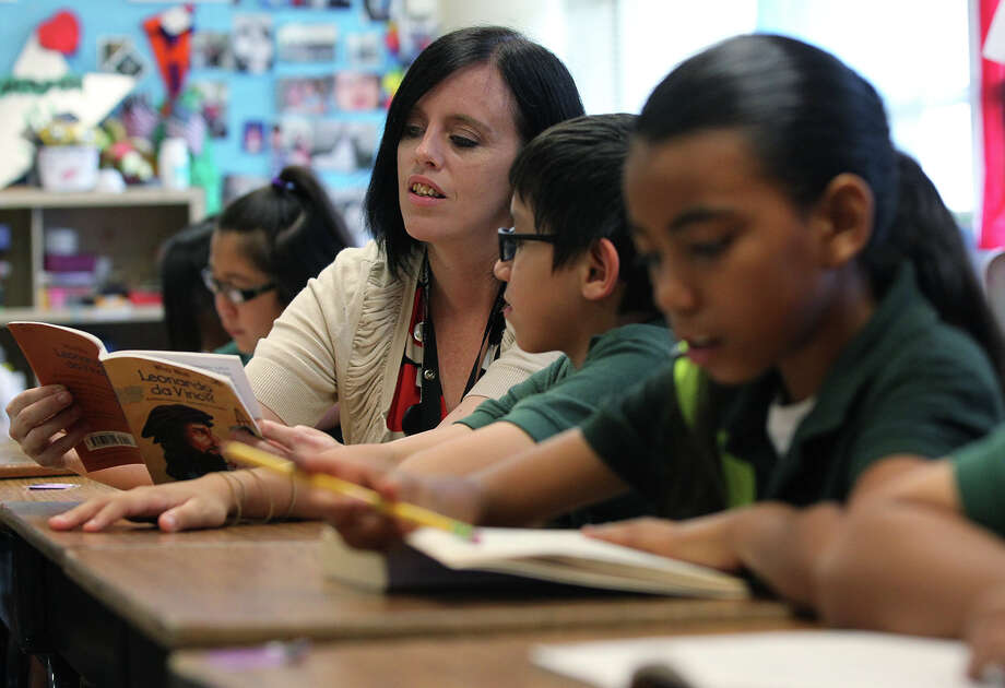 Pershing Elementary School fourth-grade teacher Jennifer Emerson, left, goes over material with Joshua Acosta, 9, on Thursday, June 6, 2013. Photo: San Antonio Express-News / © 2013 San Antonio Express-News