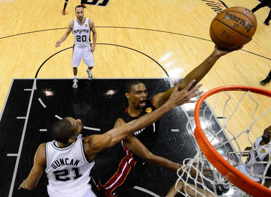 Chris Bosh shoots over Tim Duncan. Photo: Pool, Getty Images