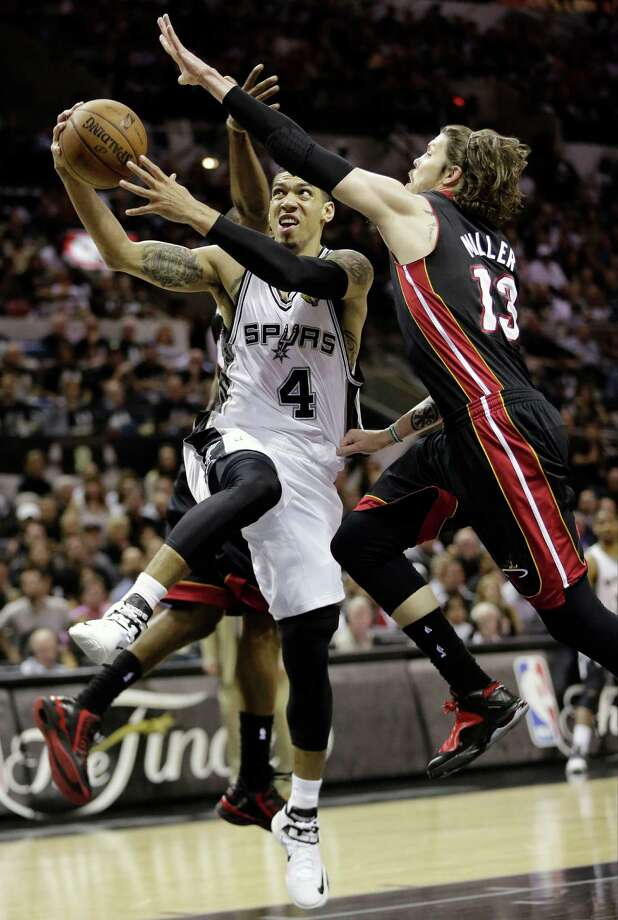 San Antonio Spurs' Danny Green (4) shoots between Miami Heat's Mario Chalmers, rear, and Mike Miller (13) during the first half at Game 5 of the NBA Finals basketball series, Sunday, June 16, 2013, in San Antonio. (AP Photo/Eric Gay) Photo: Eric Gay