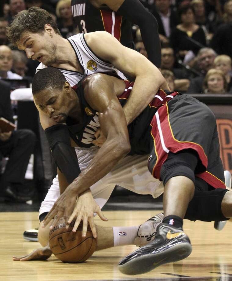San Antonio Spurs' Tiago Splitter and Miami Heat's Chris Bosh scramble for a loose ball during the first half of Game 5 of the NBA Finals at the AT&T Center on Sunday, June 16, 2013. (Kin Man Hui/San Antonio Express-News)