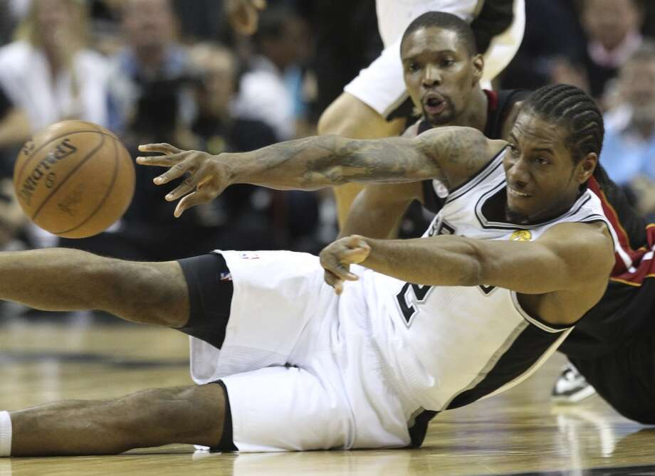 San Antonio Spurs' Kawhi Leonard and Miami Heat's Chris Bosh scramble for a loose ball during the first half of Game 5 of the NBA Finals at the AT&T Center on Sunday, June 16, 2013. (Kin Man Hui/San Antonio Express-News)