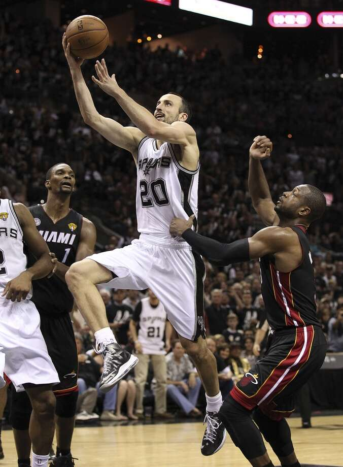 San Antonio Spurs' Manu Ginobili drives the lane for a basket against Miami Heat's Dwyane Wade during the second half of Game 5 of the NBA Finals at the AT&T Center on Sunday, June 16, 2013. (Kin Man Hui/San Antonio Express-News)