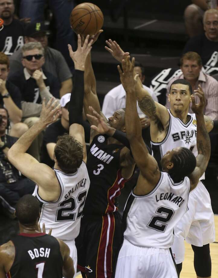 Miami Heat's Dwyane Wade tries to shoot between Spurs defenders Tiago Splitter, Kawhi Leonard, and Danny Green during the fist half of Game 5 of the NBA Finals at the AT&T Center on Sunday, June 16, 2013. (Jerry Lara/San Antonio Express-News)