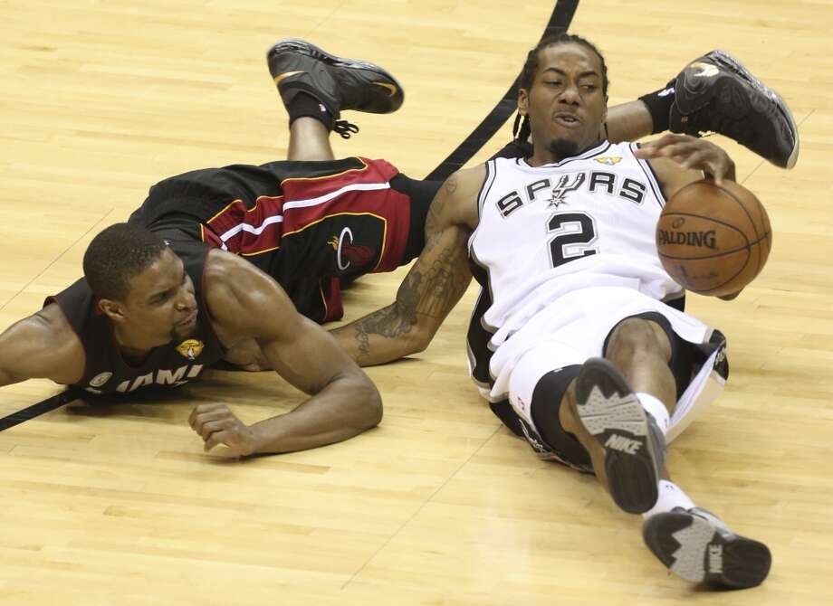 Miami Heat's Chris Bosh and San Antonio Spurs' Kawhi Leonard scramble for a loose ball during the fist half of Game 5 of the NBA Finals at the AT&T Center on Sunday, June 16, 2013. (Jerry Lara/San Antonio Express-News)