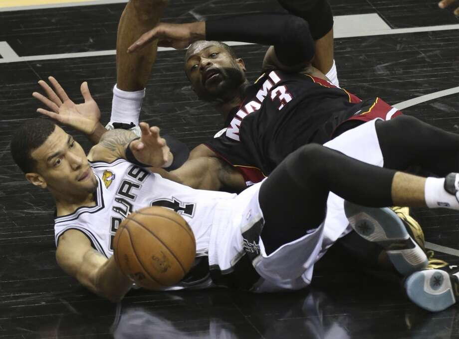 San Antonio Spurs' Danny Green and Miami Heat's Dwyane Wade scramble for a loose ball during the second half of Game 5 of the NBA Finals at the AT&T Center on Sunday, June 16, 2013. (Jerry Lara/San Antonio Express-News)
