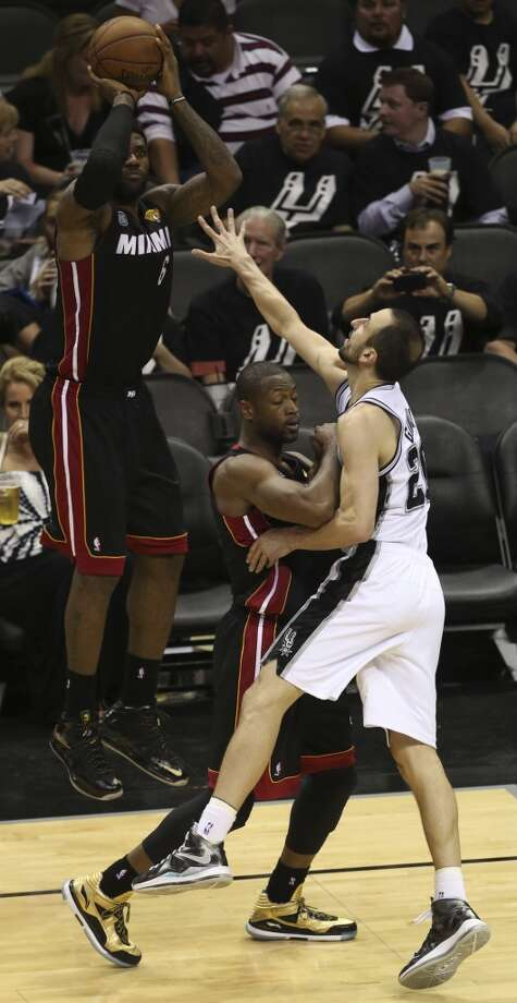 Miami Heat's LeBron James shoots from outside the three point line while San Antonio Spurs' Manu Ginobili is blocked by Dwyane Wade during the second half of Game 5 of the NBA Finals at the AT&T Center on Sunday, June 16, 2013. (Jerry Lara/San Antonio Express-News)
