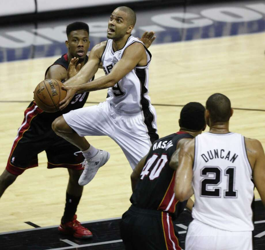 Tony Parker, splitting the defense of Miami's Norris Cole (left) and Udonis Haslem on his way to the rim, led the Spurs with a game-high 26 points. Photo: Edward A. Ornelas / San Antonio Express-News