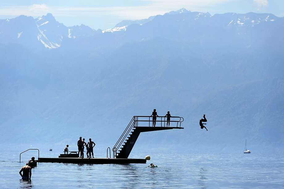 Backdropped by the French alps, kids jump into  Geneva Lake and enjoy the sunny and warm weather, in Lutry Beach near Lausanne, Southwestern Switzerland, Sunday, June 16, 2013. (AP Photo/Keystone,Laurent Gillieron) Photo: Laurent Gillieron, Associated Press
