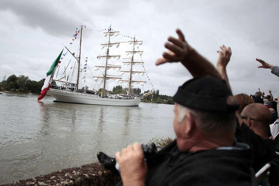 """TOPSHOTS Spectators wave at the sailors of the mexican ship the """"Cuauthemoc"""" sailing on the Seine river on the last day of the """"Armada"""" sailing boat meeting, on June 16, 2013 in Duclair. The festival is one of the world's largest meetings of tall sailing ships and war vessels. AFP PHOTO/CHARLY TRIBALLEAUCHARLY TRIBALLEAU/AFP/Getty Images Photo: Charly Triballeau, AFP/Getty Images"""