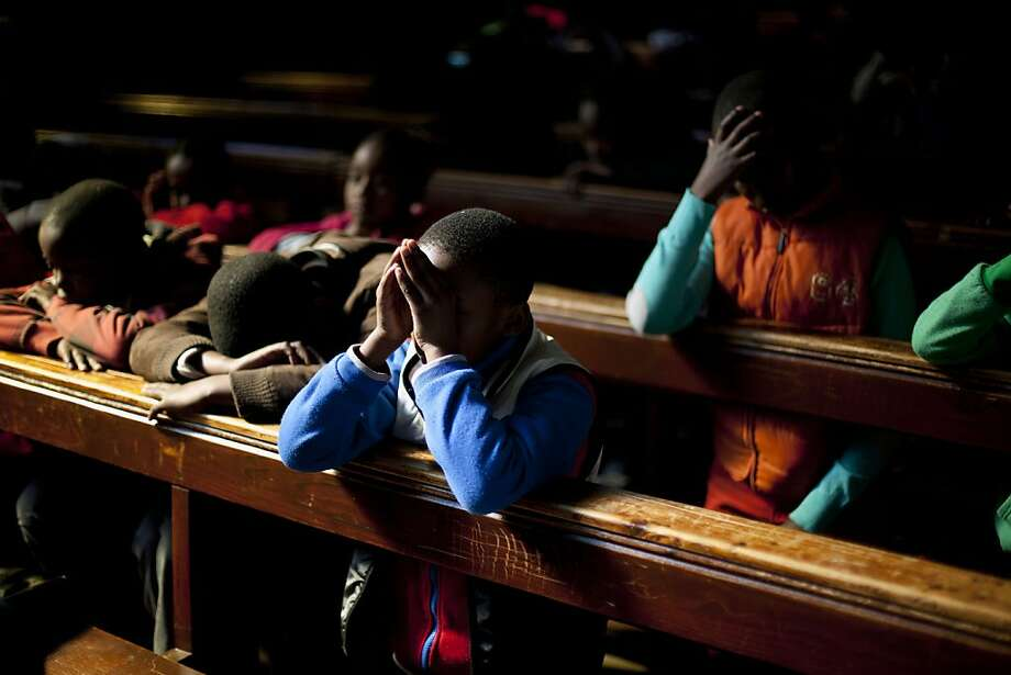 School children pray in the Regina Mundi church in Soweto township on the outskirt of  Johannesburg, South Africa, Sunday June 16, 2013.  Former South African president Nelson Mandela remained hospitalized for the ninth day with an occurring lung infection. (AP Photo/Jerome Delay) Photo: Jerome Delay, Associated Press