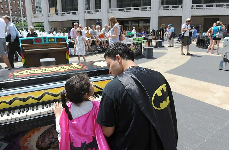 IMAGE DISTRIBUTED FOR SING FOR HOPE - Warren Alvarez and his daughter Delilah, 5, of Queens, enjoy Father's Day by playing one of the 88 Sing for Hope Pianos, supported by Chobani, Inc., at the Josie Robertson Plaza at Lincoln Center, Sunday, June 16, 2013, in New York.  The event celebrates the conclusion of the Sing for Hope Pianos project, a two-week public art installation around the five boroughs of New York.  (Photo by Diane Bondareff/Invision for Sing for Hope/AP Images) Photo: Diane Bondareff, Associated Press