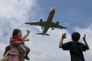 Jyoti Bisbey and her children from left, Ansuya, 5, Arnav, 2, and Mohit, 9, wave from Gravelly Point Park at planes as they roar overhead landing at Ronald Reagan Washington National Airport,  Sunday, June 16, 2013, in Arlington, Va. (AP Photo/Carolyn Kaster)