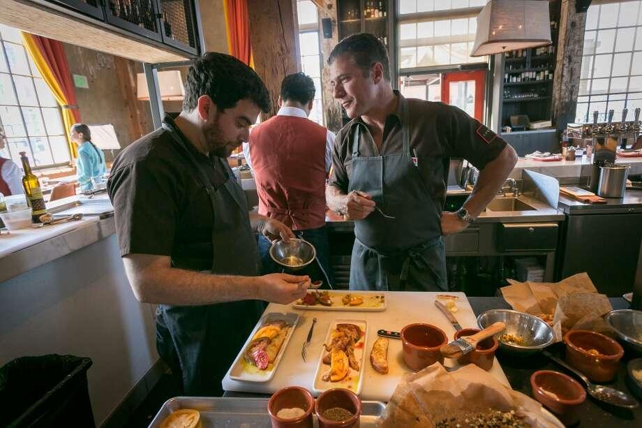 Chef Michael Chiarello talks with Chef de Cuisine Ryan McIlwraith at at Coqueta.