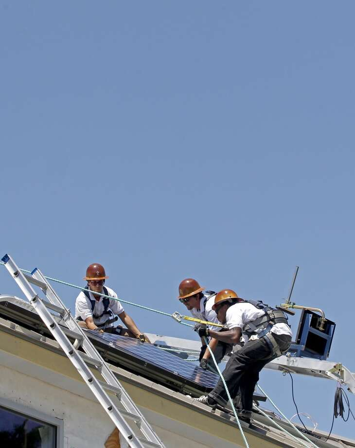 6/3/2013: From top to bottom, Brady Miller, Anthony Duplantis and Jeremy Young with Texas Solar Outfitters install solar panels in a new constructed home located in the Dominion Falls subdivision in Humble, Texas. Photo: Houston Chronicle