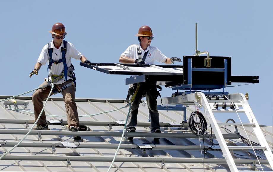 6/3/2013: From left to right,  Brady Miller and Anthony Duplantis with Texas Solar Outfitters install solar panels in a new constructed home located in the Dominion Falls subdivision in Humble, Texas. Photo: Houston Chronicle