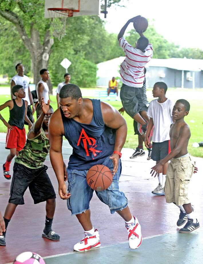 Defensive tackle for the Miami Dolphins and Monsignor Kelly Catholic High School graduate, Kheeston Randall, plays basketball with the kinds in attendance at the Danny Gorrer Annual Cookout at Barbara Jacket Park in Port Arthur on June 15, 2013. Photo taken: Randy Edwards/The Enterprise Photo: Randy Edwards