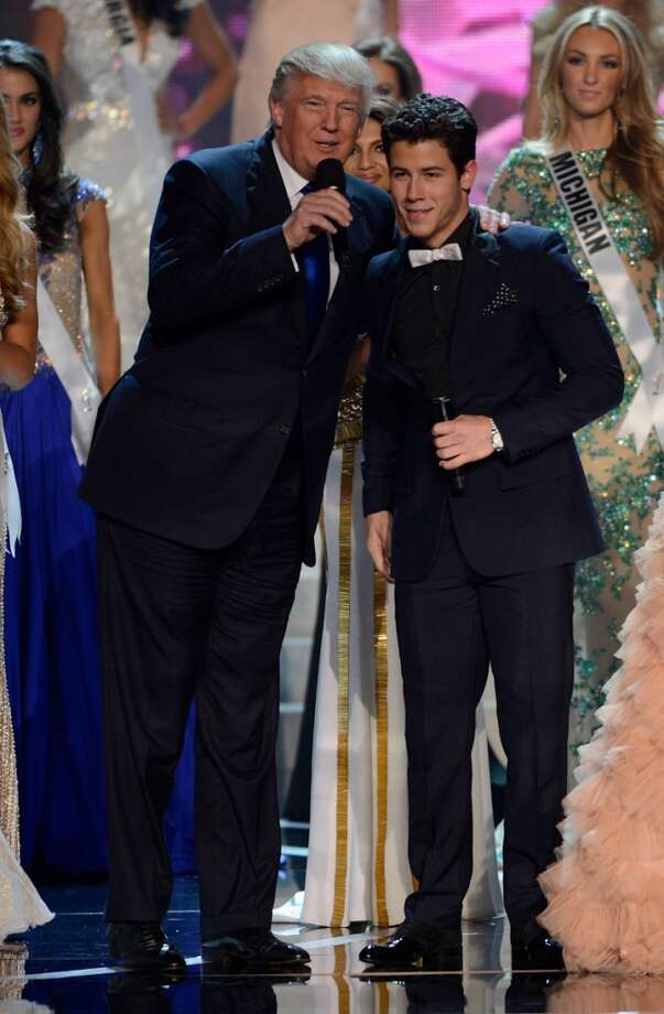From left, Donald Trump and recording artist and host Nick Jonas joke around onstage during the Miss USA 2013 pageant, Sunday, June 16, 2013, in Las Vegas.