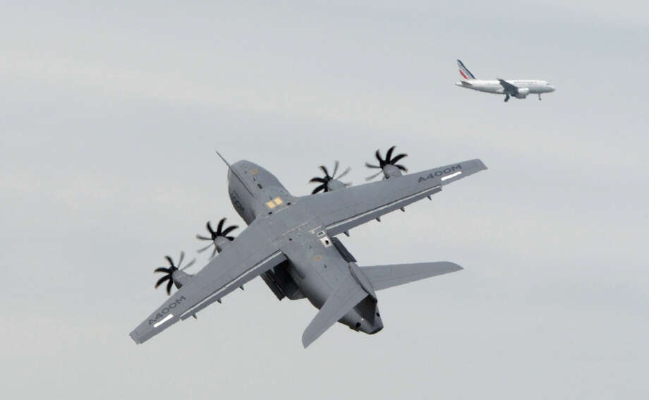 Pilots of an Airbus A400M present their flying display during a preparation at  Le Bourget on June 16, 2013 as an Air France plane crosses the sky far in the background on the eve of the opening of  the Paris Air show. Photo: AFP, AFP/Getty Images / 2013 AFP