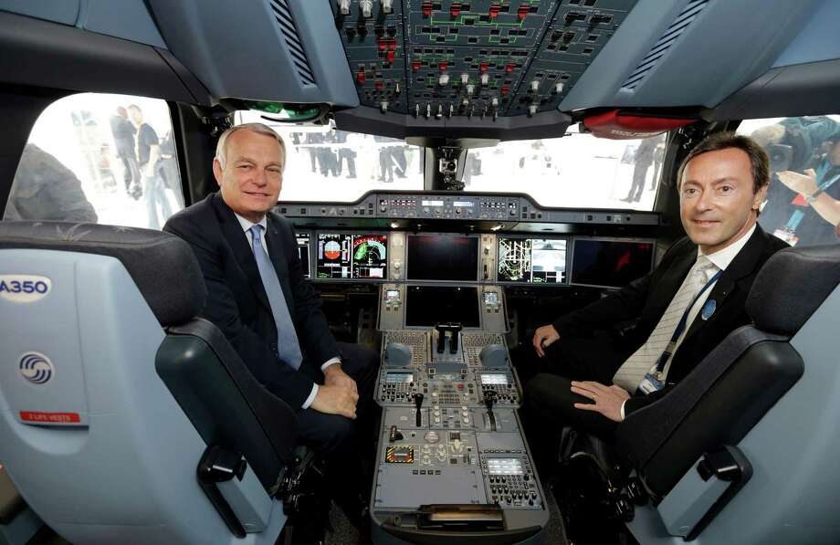 French Prime Minister Jean-Marc Ayrault (left) and Airbus President and CEO Fabrice Bregier pose in an Airbus A350 passenger aircraft flight deck replica during the opening visit of the 50th Paris Air Show, at Le Bourget airport near Paris, on June 17, 2013. Photo: PHILIPPE WOJAZER, AFP/Getty Images / 2013 AFP