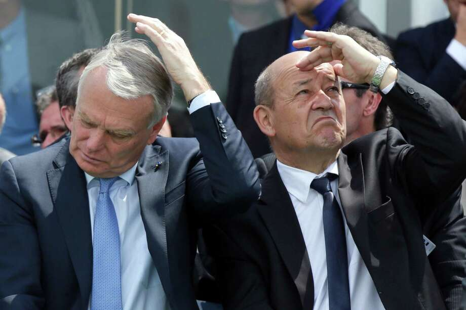 French Prime Minister Jean-Marc Ayrault (left) and Defense Minister Jean-Yves Le Drian attend flight demonstrations during the opening of the 50th Paris Air Show, at Le Bourget airport near Paris, on June 17, 2013. Photo: PHILIPPE WOJAZER, AFP/Getty Images / 2013 AFP