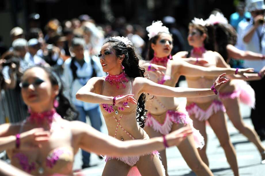 Kayla Issac (center) of the group Hot Pink Feathers as they dance their way down 24th St. during the 35th annual Carnaval parade in the Mission District of San Francisco on May 26th, 2013.